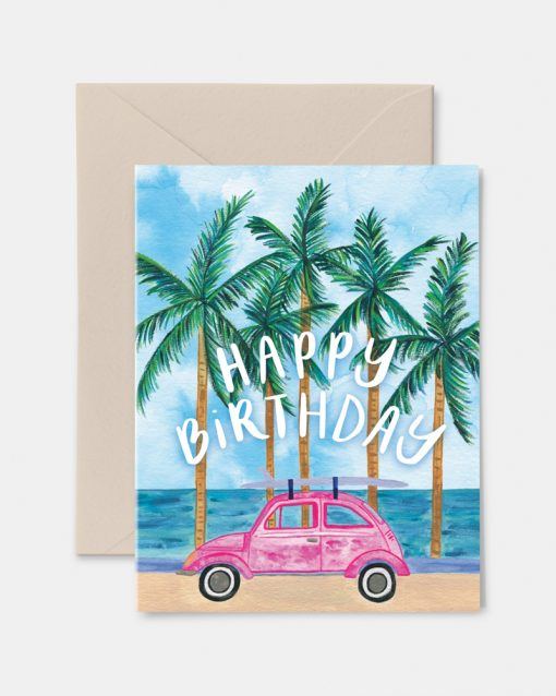 Birthday card featuring a small car surrounded by palm trees and the water