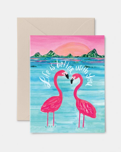 Two flamingos standing the water with the sunset behind them.