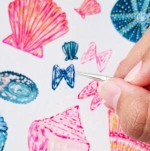 Closeup of Renee's hand painting seashells